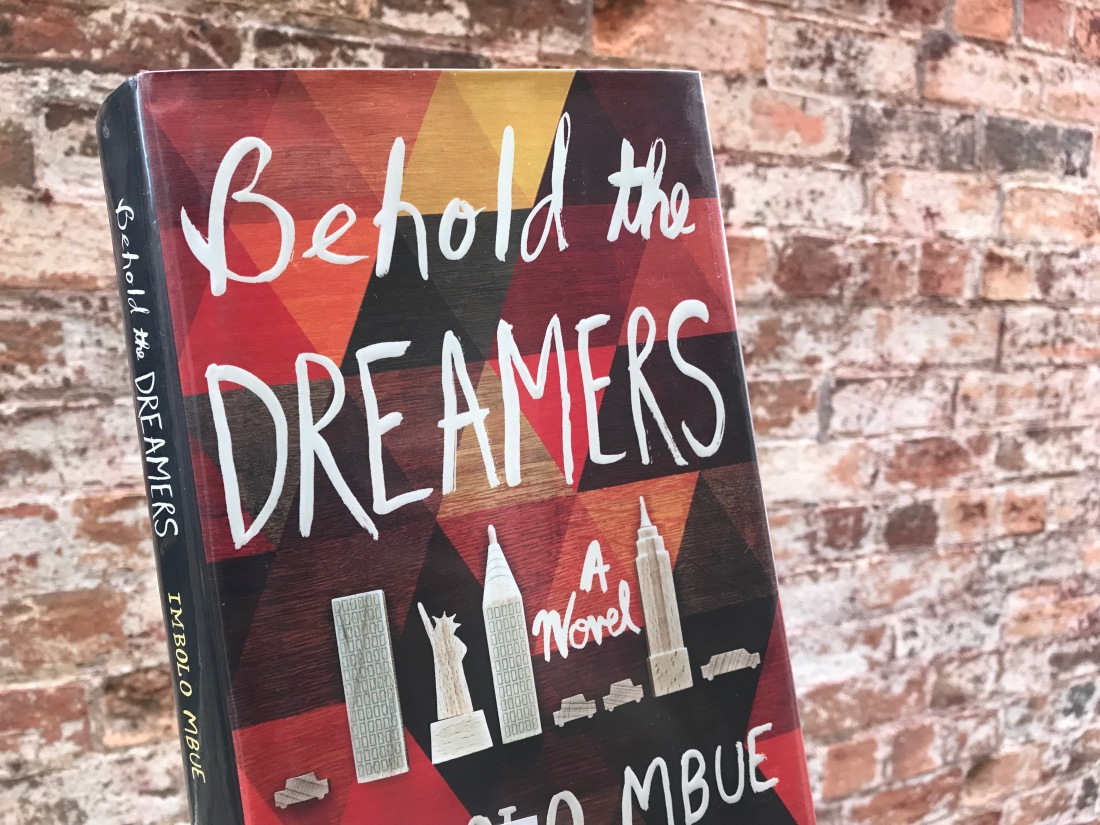 Behold the Dreamers book by Imbolo Mbue against brick wall