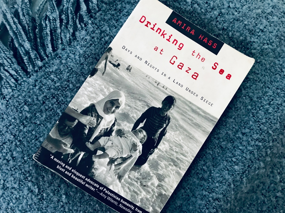 drinking the sea at gaza book on blue blanket