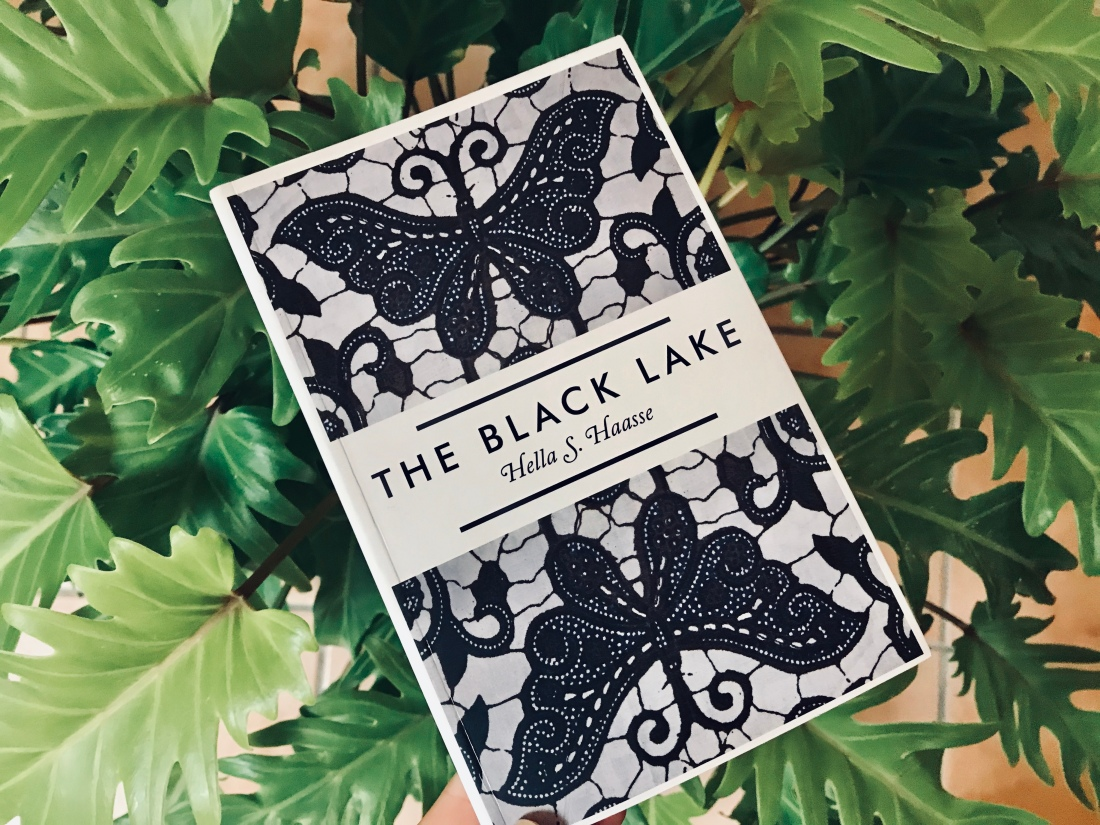 the black lake cover with dark butterflies symmetrical and against a backdrop of leaves