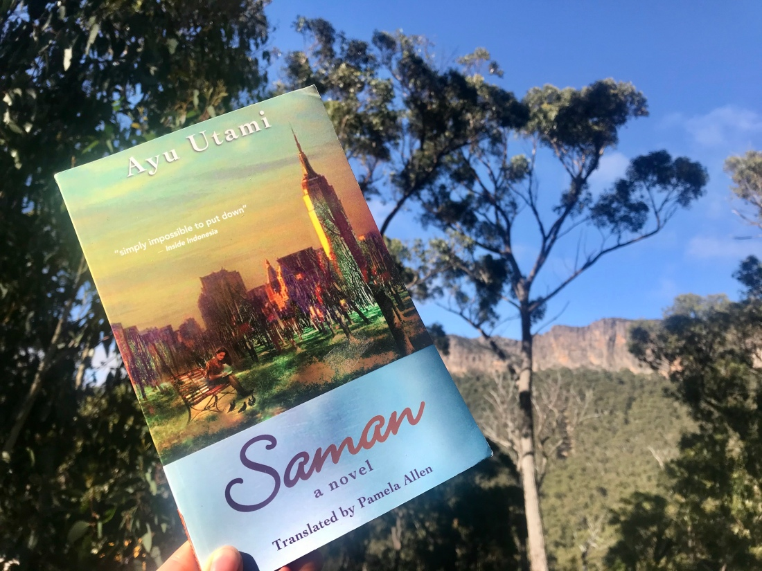 Saman book with cover of woman writing on park bench and Empire State building in backdrop; book against blue sky and trees