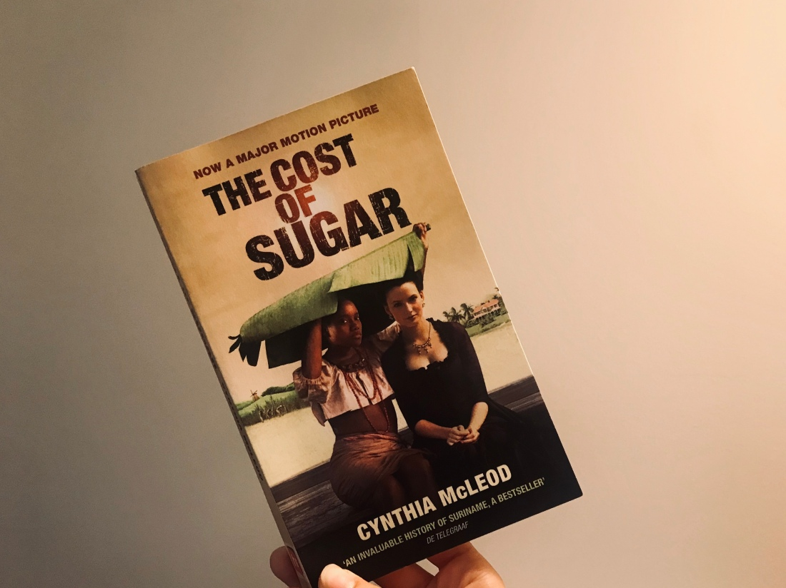 The Cost of Sugar book with Sarith and Minimini on front cover under big leaf