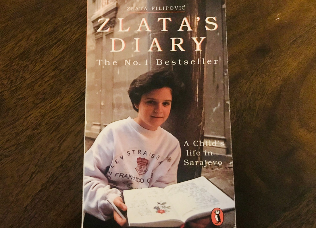photo of Zlata holding her diary as book cover, wooden desk behind