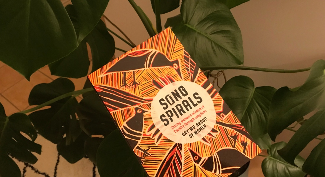 Song Spirals book in front of monstera plant, with cover image by Gaymala Yunupinu