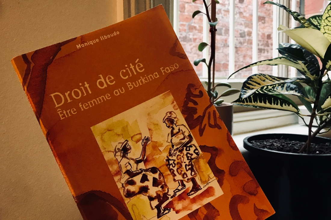orange book with two women chatting on cover, plants in background