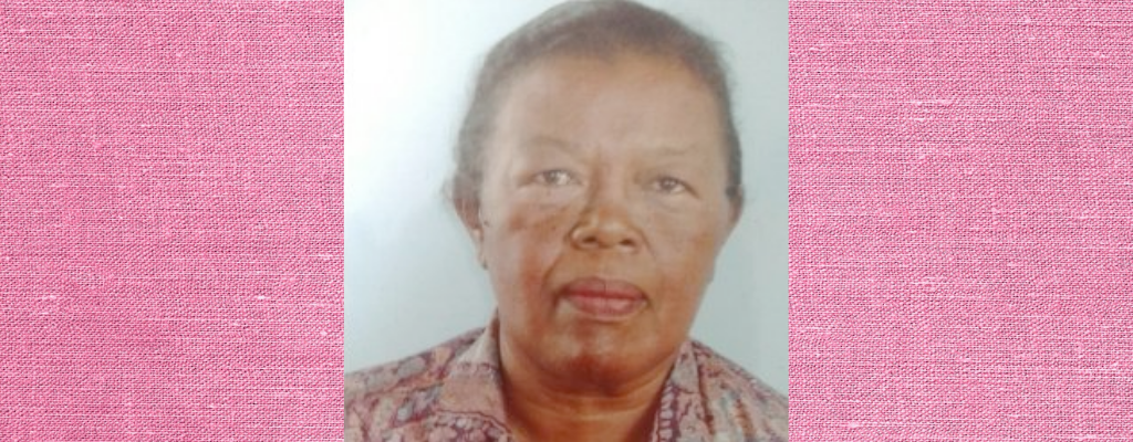 Photo of Cyprienne with hair tied back and pink shirt on, against pink background