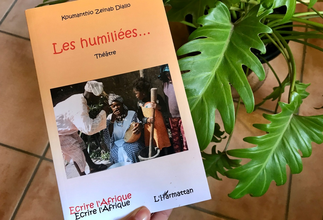 Guinean family outdoors in conversation on cover of book, held against plant