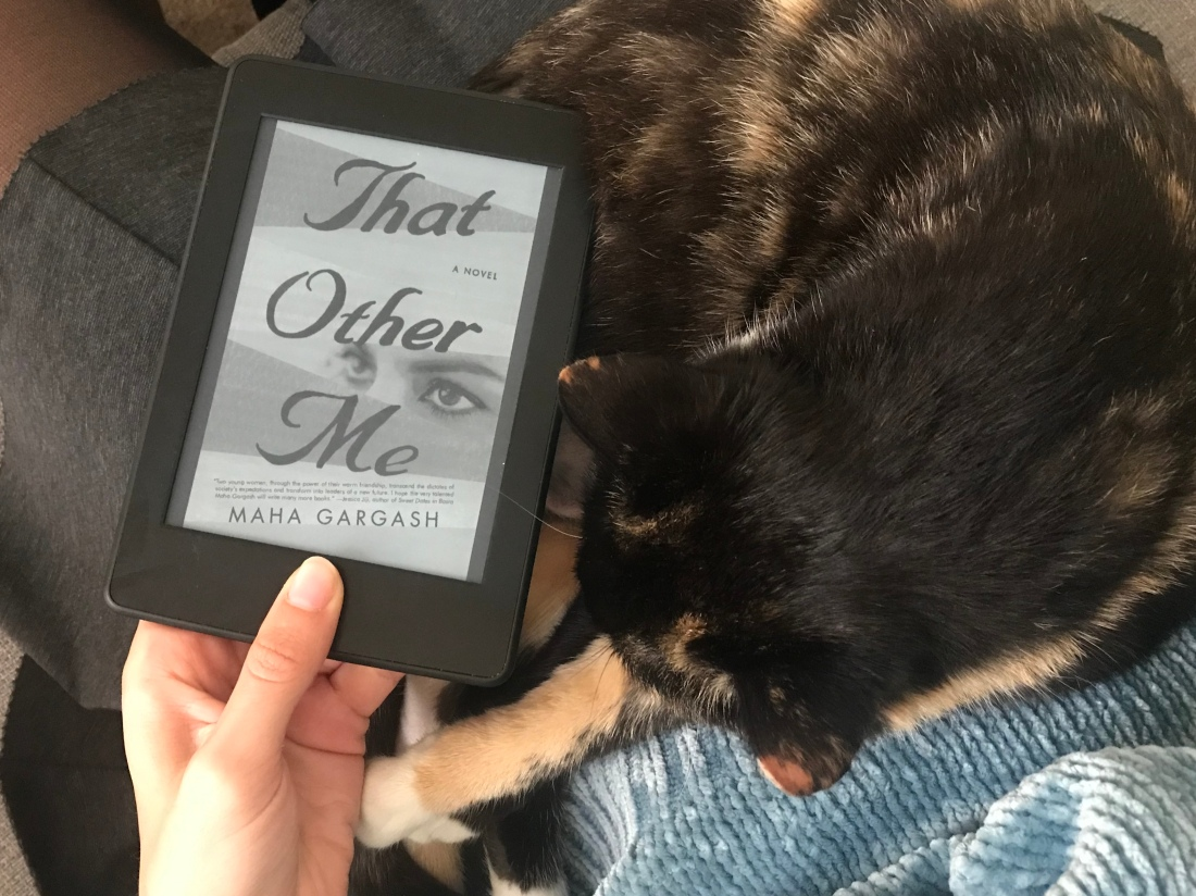 book cover with eye watching, next to cat on lap