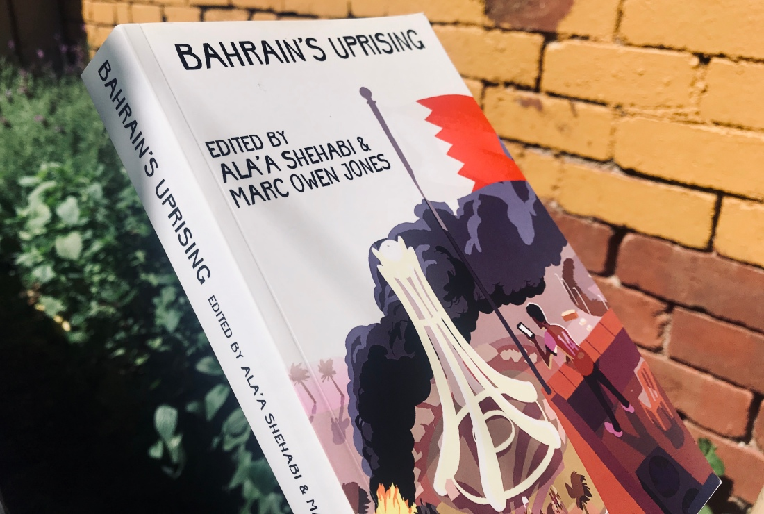Bahrain Uprising book against yellow wall - cover shows Pearl Roundabout